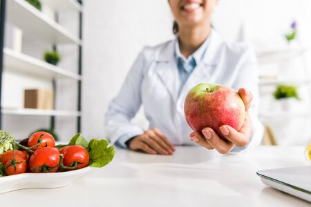 cropped view of nutritionist holding tasty apple near vegetables