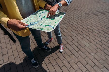 Cropped view of travelers standing on street and pointing with finger at map