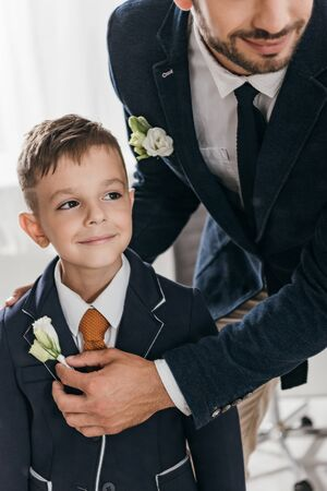 cropped view of dad and son in jackets with boutonnieres