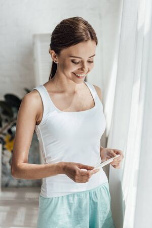 smiling young woman holding pregnancy test at home