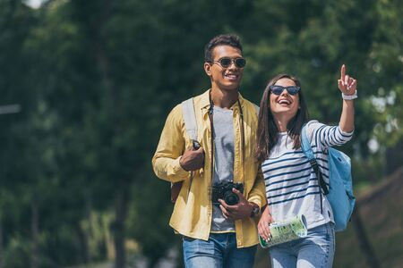 happy girl in sunglasses pointing with finger near mixed race man with digital camera