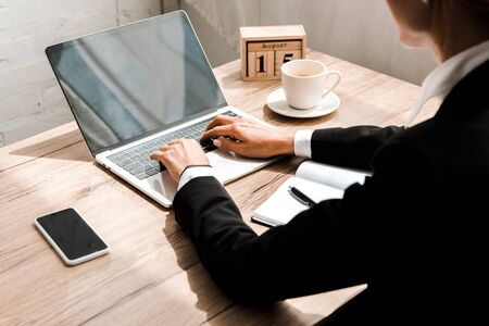 selective focus of woman typing on laptop near wooden cubes with calendar and smartphone with blank screen