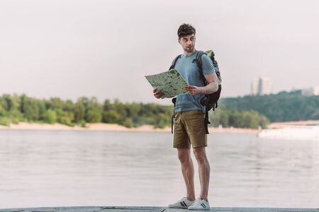 handsome man in t-shirt and shorts holding map and looking away
