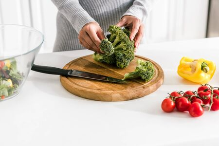cropped view of woman holding green broccoli near bowl and fresh vegetables 写真素材