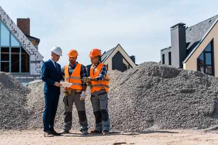 constructors standing near businessman with digital tablet