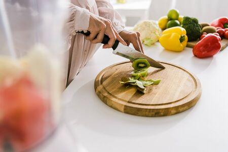 selective focus of pregnant woman cutting kiwi on chopping board