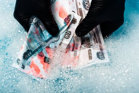 top view of man in rubber gloves washing russian money in soap bubbles with water Stock Photo