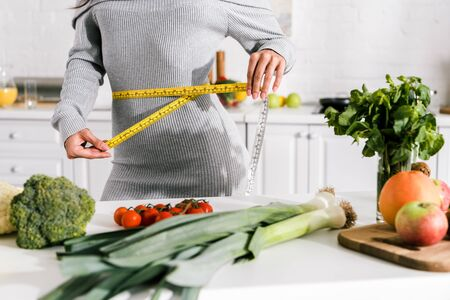 cropped view of woman measuring waist near vegetables on table 写真素材