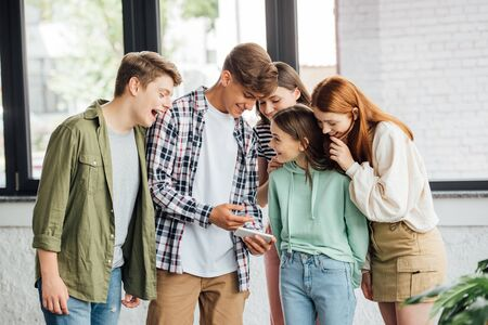group of happy friends laughing while using smartphone Фото со стока