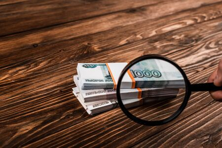 cropped view of man holding magnifier near russian money on table