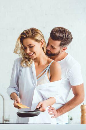 handsome man hugging happy girlfriend preparing pancake on frying pan Banque d'images - 131261479