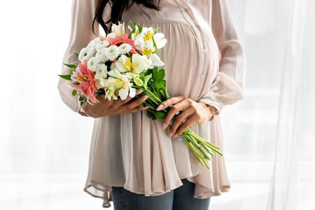 cropped view of pregnant african american woman holding bouquet in apartment
