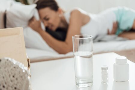 selective focus of suffering woman in bed and pills with glass of water on foreground