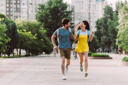 handsome man and asian woman running and looking at each other