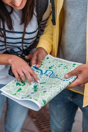 Cropped view of tourists holding and pointing with finger at map