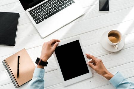 cropped view of woman holding digital tablet with blank screen near gadgets and cup of coffee
