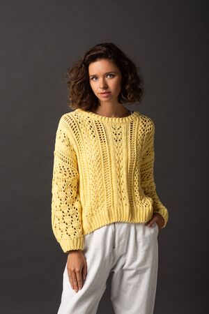 curly woman in yellow sweater with hand in pocket on black background