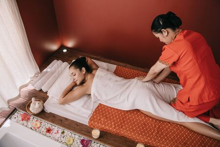 high angle view of masseur doing foot massage to woman in spa salon Stock Photo