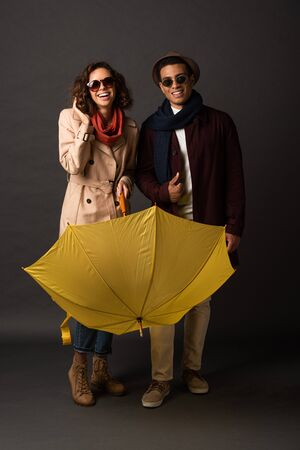 happy stylish interracial couple in autumn outfit with yellow umbrella on black background Banco de Imagens