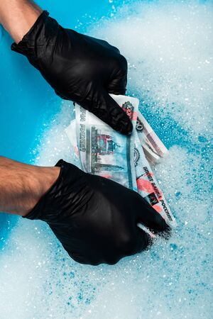 overhead view of man in black rubber gloves washing russian money in soap bubbles