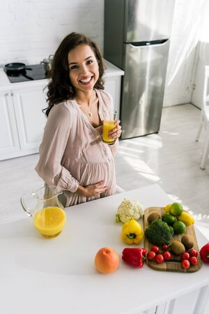 overhead view of happy pregnant woman smiling while holding glass with orange juice