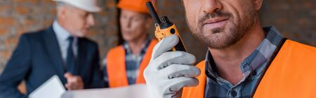 panoramic shot of bearded man holding walkie talkie