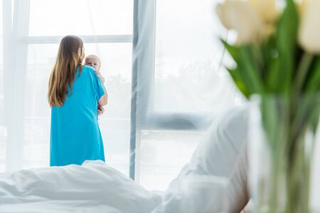 selective focus of young mother holding her child in hospital
