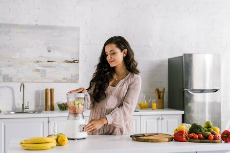happy pregnant woman touching button on blender with fruits