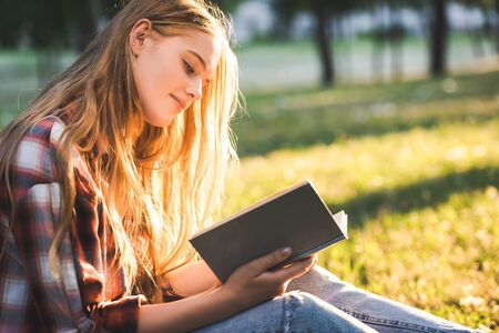 side view of beautiful girl in casual clothes sitting on meadow in sunlight and reading book Zdjęcie Seryjne