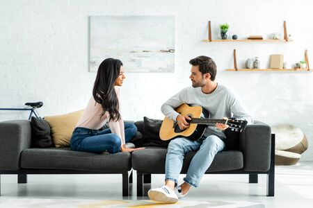 side view of smiling african american woman looking at man with acoustic guitar