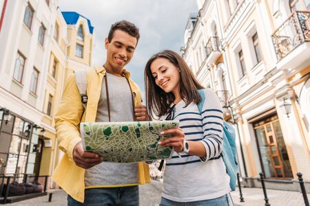 low angle view of cheerful mixed race man holding map near happy girl