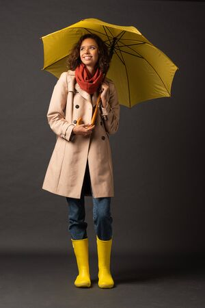 smiling woman in trench coat and rubber boots holding yellow umbrella and looking away on black background
