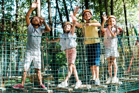 cheerful multicultural boys near friends in helmets waving hands in adventure park