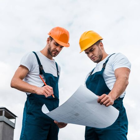 low angle view of handsome builders in uniform looking at paper with plan