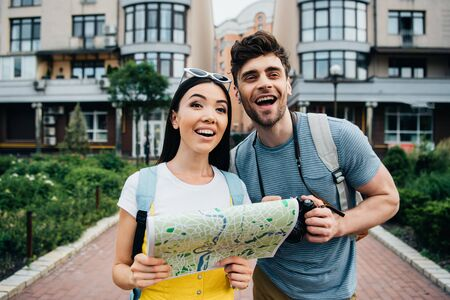 handsome man looking away and asian woman holding map