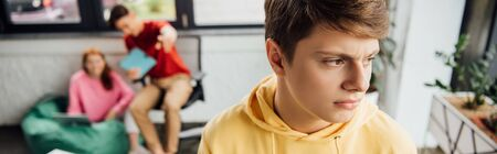 panoramic shot of pensive boy in yellow hoodie and laughing classmates bullying him