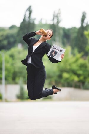 elegant businesswoman holding newspaper and drinking coffee to go while levitating on street