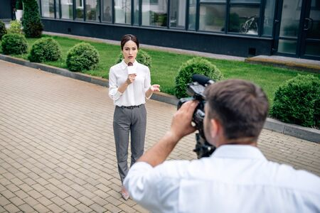 selective focus of attractive journalist holding microphone and cameraman shooting her outside
