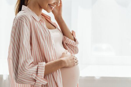 partial view of happy pregnant woman smiling and touching belly