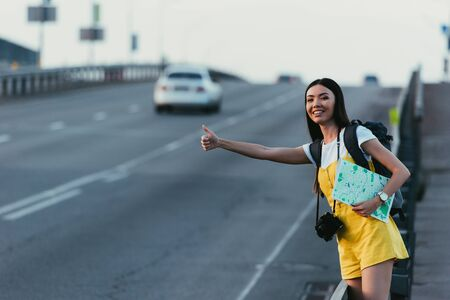 asian woman in yellow overalls hitchhiking and holding map 스톡 콘텐츠