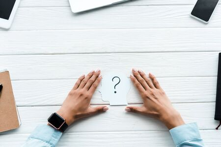 top view of woman touching paper with question mark near gadgets on table