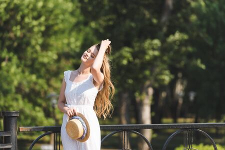 beautiful girl in white dress holding straw hat while standing with closed eyes and touching hair