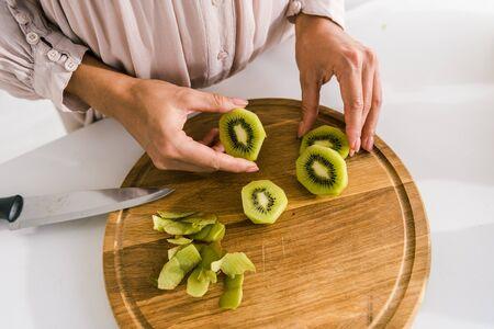 cropped view of pregnant woman holding slice of kiwi Stok Fotoğraf