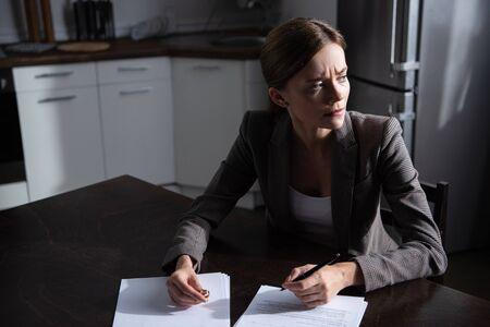 smutna młoda kobieta przy stole z dokumentami rozwodowymi