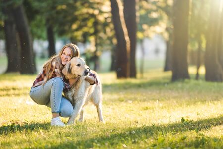 full length view of beautiful young girl in casual clothes hugging golden retriever while sitting on meadow in sunlight and looking at camera
