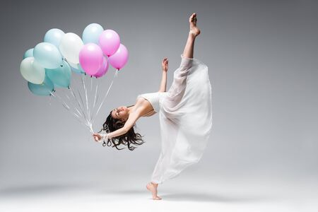 graceful ballerina in white dress dancing with festive balloons on grey background Reklamní fotografie