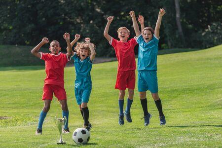 fröhliches multikulturelles Gestikulieren in der Nähe von Trophäen und Fußball