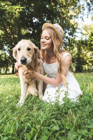 beautiful young girl in white dress and straw hat petting golden retriever while smiling, sitting on meadow and looking at dog
