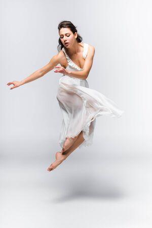 Atractiva y elegante bailarina en vestido blanco bailando sobre fondo gris Foto de archivo