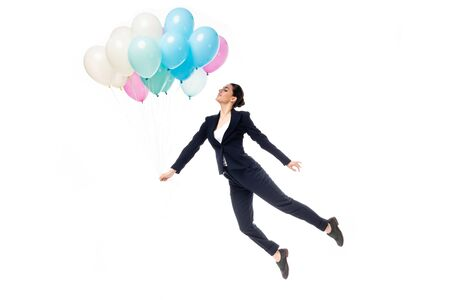 happy businesswoman in formal wear levitating with festive balloons isolated on white Stock fotó
